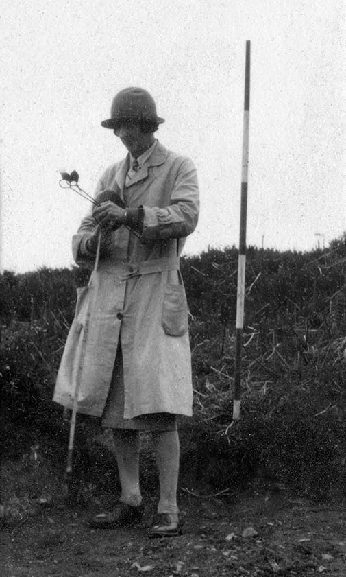 Dorothy Liddell with tape, surveyors arrows and an imperial ranging pole